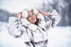 Gelukkige vrouw die pret op de sneeuw in de winterbos hebben Royalty-vrije Stock Foto's