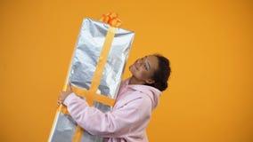 Gelukkige vrouw die reusachtige giftbox op gele achtergrond, verrassing, levering houden stock video