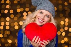 Gelukkige vrouw die rood hart over de achtergrond van vakantielichten houden Stock Afbeeldingen