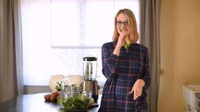Gelukkige vrouw die selderie in keuken eten stock videobeelden
