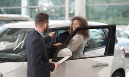Gelukkige vrouw die sleutelsoh nieuwe auto van manager nemen royalty-vrije stock afbeeldingen