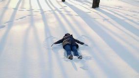 Gelukkige vrouw die sneeuwengelen maken stock video