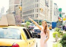 Gelukkige vrouw die taxicabine in de stad van Manhattan begroeten New York Royalty-vrije Stock Fotografie