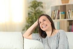 Gelukkige vrouw die thuis omhoog het kijken dromen royalty-vrije stock afbeeldingen