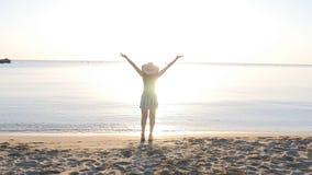 Gelukkige vrouw die travaler op het strand terug naar camera lopen stock video