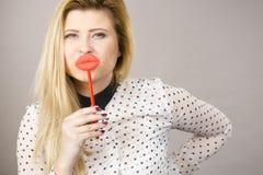 Gelukkige vrouw die valse lippen op stok houden Stock Fotografie