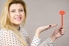 Gelukkige vrouw die valse lippen op stok houden Stock Afbeelding