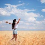 Gelukkige vrouw die van het leven op de schoonheid van de gebiedsaard, de blauwe hemel en het gebied met gouden tarwe genieten Op stock afbeeldingen