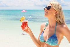 Gelukkige vrouw die verse en smakelijke cocktail op het strand houden Stock Afbeelding