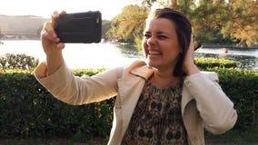 Gelukkige vrouw die videotelefoongesprek van meer in park in vakantie in Europees maken stock video