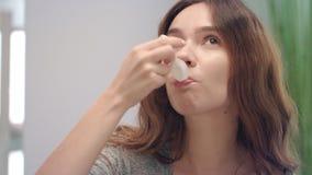 Gelukkige vrouw die vloeibare stroop voor helende hoest in badruimte drinken stock footage