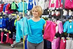 Gelukkige vrouw die voor babysportkleding winkelen in winkel Royalty-vrije Stock Afbeeldingen