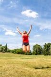 Gelukkige vrouw die voor voltooiing en succes springen royalty-vrije stock fotografie