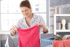 Gelukkige vrouw die wasserij doet stock afbeeldingen