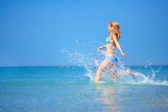 Gelukkige vrouw die in zeewater lopen Stock Afbeelding