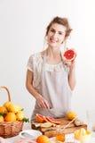 Gelukkige vrouw die zich binnen dichtbij lijst met heel wat citrusvruchten bevinden Royalty-vrije Stock Afbeelding