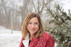 Gelukkige vrouw die zich door pijnboomboom bevinden in park terwijl de magische sneeuw is stock foto