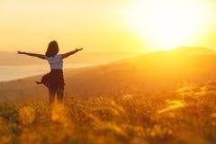 Gelukkige vrouw die zich met haar terug op zonsondergang in aard bevinden iwith ope royalty-vrije stock foto