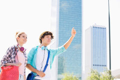 Gelukkige vrouw die zich met mannelijke vriend bevinden die een taxi in stad begroeten Royalty-vrije Stock Afbeelding