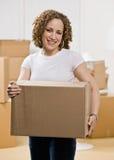 Gelukkige vrouw die zich in nieuw huis beweegt Royalty-vrije Stock Foto's