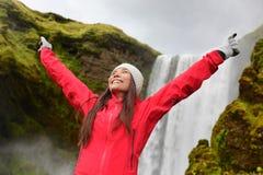 Gelukkige vrouw door waterval Skogafoss op IJsland Stock Afbeeldingen