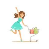 Gelukkige vrouw in een blauwe kleding die met boodschappenwagentje lopen, die in kleurrijke kruidenierswinkelopslag, supermarkt o royalty-vrije illustratie