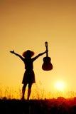 Gelukkige vrouw en gitaar met zonsondergangsilhouet Royalty-vrije Stock Foto