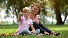 Gelukkige vrouw en jongen die duimen tonen, advertentie van sociale steun voor enige moeders stock afbeelding