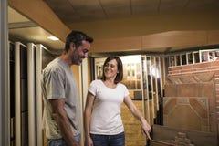 Gelukkige vrouw en man die keramische tegel voor badkamers bekijken royalty-vrije stock afbeelding