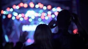Gelukkige vrouw en man golvende handen en het dansen bij muziekfestival, nachtleven stock video
