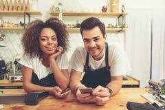 Gelukkige vrouw en man holdingstelefoons bij cafetaria royalty-vrije stock afbeelding