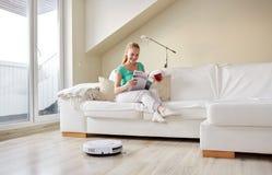 Gelukkige vrouw en robot stofzuiger thuis Royalty-vrije Stock Afbeelding