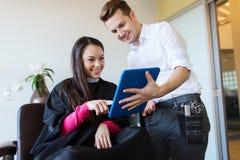 Gelukkige vrouw en stilist met tabletpc bij salon stock foto's