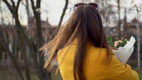 Gelukkige vrouw in gele laag die met rozen dansen De dagconcept van de valentijnskaart ` s Meisje in liefde Langzame Motie stock footage