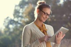 Gelukkige vrouw in glazen die tabletpc met behulp van