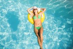 Gelukkige vrouw in groene bikini die op opblaasbare buis in zwembad drijven Royalty-vrije Stock Foto's