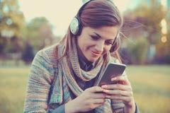 Gelukkige vrouw het letten op video's in een slimme telefoon royalty-vrije stock afbeeldingen