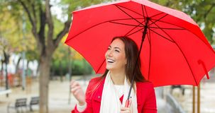 Gelukkige vrouw in het rode lopen onder de regen stock video
