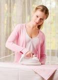 Gelukkige vrouw het strijken kleren Stock Afbeelding