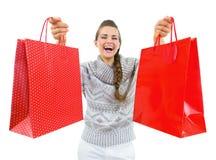 Gelukkige vrouw in Kerstmishoed die Kerstmis het winkelen zakken tonen stock afbeelding