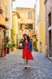Gelukkige vrouw in kleding en hoed die op bedekte straat lopen Stock Afbeelding