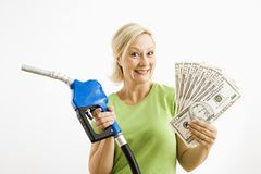 Gelukkige vrouw met benzinepomp en geld. Stock Foto