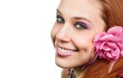 Gelukkige vrouw met bloem bij oor die op wit wordt geïsoleerd, stock afbeeldingen