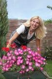 Gelukkige vrouw met bloemen in haar tuin Royalty-vrije Stock Foto