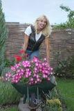 Gelukkige vrouw met bloemen in haar tuin Stock Afbeelding
