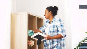 Gelukkige vrouw met doek die thuis bestrooien stock video