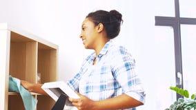 Gelukkige vrouw met doek die thuis bestrooien stock videobeelden