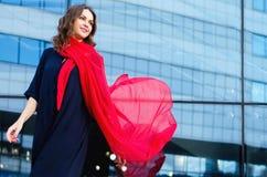 Gelukkige vrouw met een sjaal Portret van het mooie meisje Modieus portret van een meisjesmodel met golvende rode zijdesjaal Stock Foto's