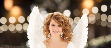Gelukkige vrouw met engelenvleugels over Kerstmislichten royalty-vrije stock afbeeldingen