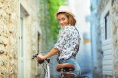 Gelukkige vrouw met fiets op straat van oude stad Stock Foto